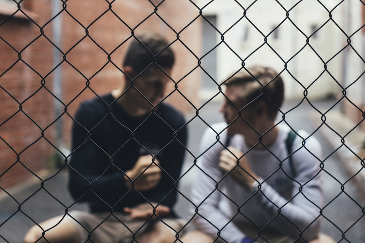 two young men talking behind fence